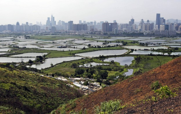 In this April 10, 2014 photo, the southern Chinese megacity of Shenzhen is visible from the hills of Hong Kong, the former British colony next door. Shenzhen's economy is booming as the former fishing village undergoes its latest transformation, from a manufacturing hub that powered China's economic rise into the country's version of Silicon valley, shedding low-cost factory production for growth staked on finance, technology and culture. (AP Photo/Kin Cheung)
