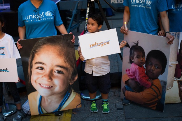 Volunteers hold photos of refugee children during a candlelight vigil held by the Children's Defense Fund - New York and UNICEF to shed light on the roughly 50 million children who are currently displaced worldwide, at Dag Hammarskjold Plaza Sunday, Sept. 18, 2016, in New York. (AP Photo/Kevin Hagen)