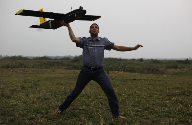 Remo Peduzzi, Managing Director, ResearchDrones LLC Switzerland prepares to fly an unmanned aircraft or drone at the Kaziranga National Park at Kaziranga in Assam state, India, Monday, April 8, 2013.Wildlife authorities used drones on Monday for aerial surveillance of the sprawling natural game park in northeastern India to protect the one-horned rhinoceros from armed poachers. The drones will be flown at regular intervals to prevent rampant poaching in the park located in the remote Indian state of Assam. The drones are equipped with cameras and will be monitored by security guards, who find it difficult to guard the whole 480-square kilometer (185-square mile) reserve. (AP Photo/Anupam Nath)