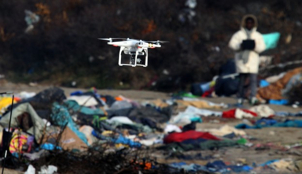 A drone belonging to a British journalist videos the Calais migrants camp after it was partially cleared, Monday, Jan.18, 2016 in Calais, northern France. Bulldozers  were used to clear a 100-meter-long strip of land between the camp and the highway. Up to 6,000 people were staying there in the fall, though the number has decreased recently. (AP Photo/Michel Spingler)